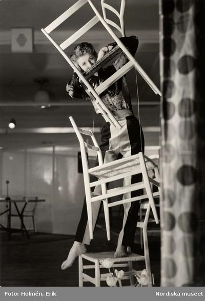 Modell poserar med upphängda trästolar. Italiana på NK (Nordiska Kompaniet) i Stockholm, 1953.