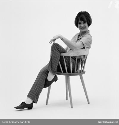 Kvinna i blus, rutiga byxor, vita strumpor och snörskor sitter på en pinnstol.