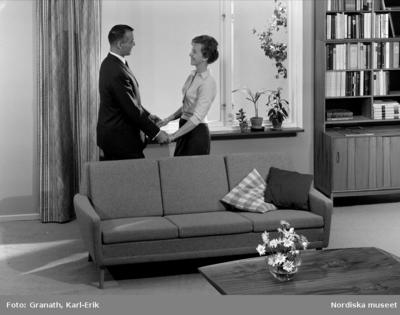 Man och kvinna i vardagsrum. De står framför fönster och håller varandras händer.