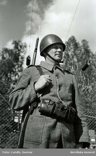 Beredskapstjänst. Landsstormssoldat med hjälm och gevär med bajonett på ryggen.