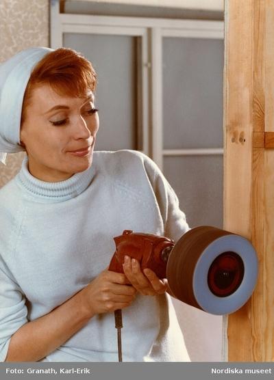 Kvinna slipar på trä med en slipskiva monterad på en borrmaskin.