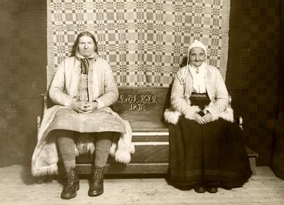 Ett äldre par sitter på en brudsoffa. Sollerön, Dalarna.