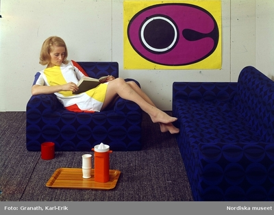 Flicka i sextiotalsinteriör, sittande i en blå soffa.
