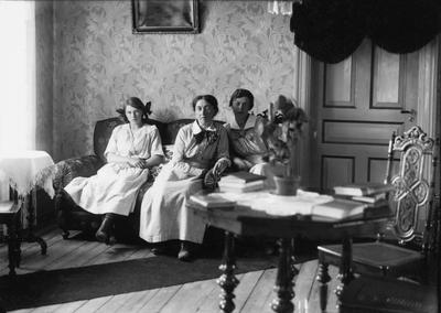 Tre kvinnor porträtteras sittande i en soffa. Lima, Dalarna
