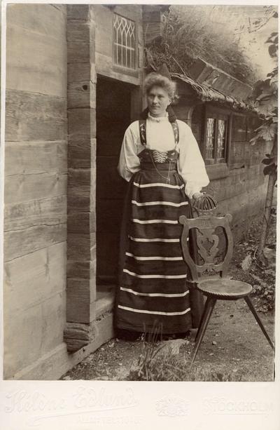 En kvinna poserar i folkdräkt från Dalarna utanför en stuga. Krönt allmogestol.