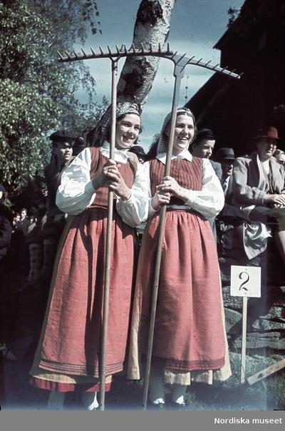 Två folkdräktsklädda kvinnor med var sin räfsa.