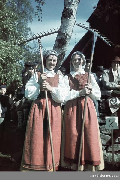 Två folkdräktsklädda kvinnor med varsin räfsa.