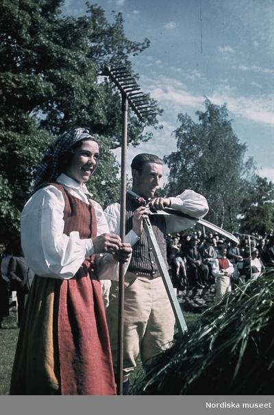 Kvinna och man klädda i folkdräkt. Kvinnan håller en räfsa, mannen håller en lie.