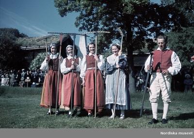 Fyra kvinnor och en man klädda i folkdräkt. Kvinnorna håller varsin räfsa, mannen håller en lie.