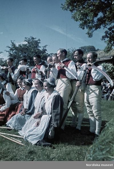 Gruppbild med folkdräksklädda personer. Kvinnorna med räfsor, männen med liar.