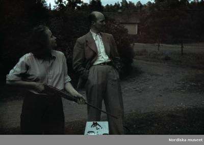 En kvinna med ett luftgevär, en man står bredvid.