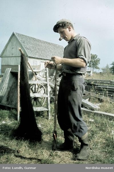 En man med pipa i munnen sysslar med fisknät.
