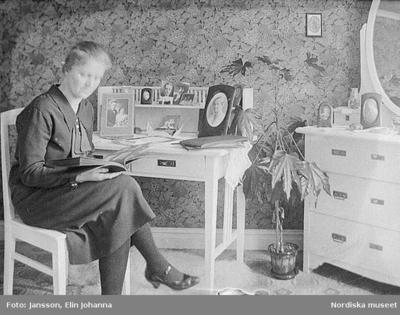 En kvinna tittar i ett fotoalbum. Lima, Dalarna.