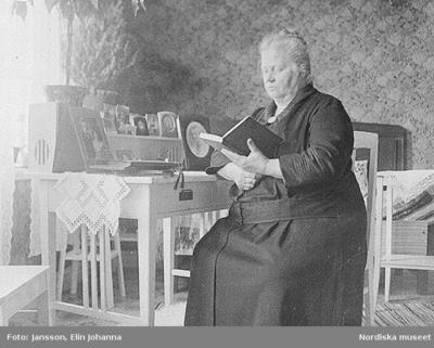 En äldre kvinna läser en bok. Lima, Dalarna.
