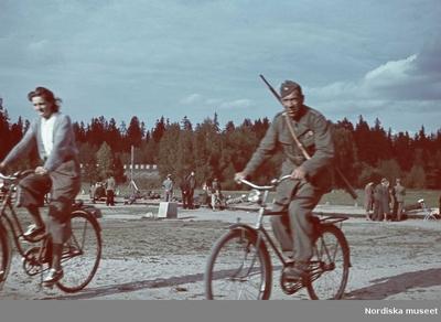 Skytteövning. I förgrunden en man och en kvinna på cyklar. Mannen är iklädd uniform bär ett gevär över axeln.