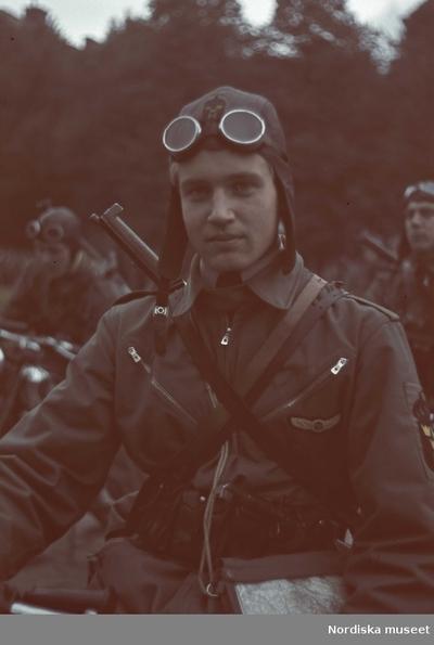 MC-ordonnans ur hemvärnet. I pannan bär han motorcykelglasögon och på ryggen en karbin.