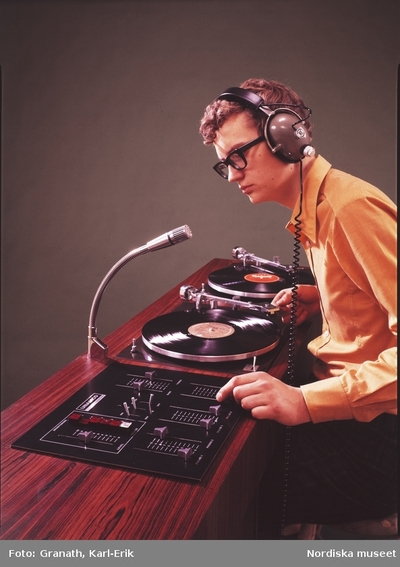 En ung man vid ett mixerbord med två skivspelare för vinylskivor och hörlurar på huvudet.