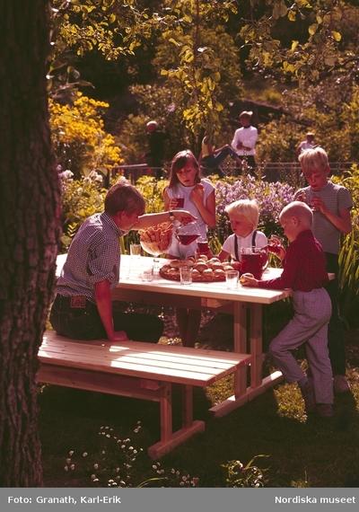 Ett sällskap av barn  runt ett dukat bord under ett träd. En av pojkarna häller upp saft. på bordet ett fat med bullar i bakgrunden lek.