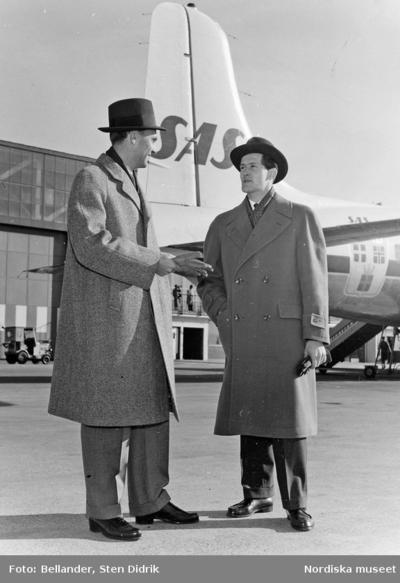 Två modeller i hatt och rock framför ett Scandinavian Airlines-flygplan.