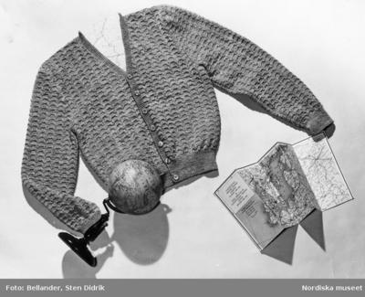 En stickad kofta, en jordglob och en karta från Scandinavian Airlines.