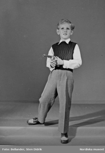 Ett barn i stickad pullover, skjorta, byxor med pressveck, snörskor och revolver i handen.