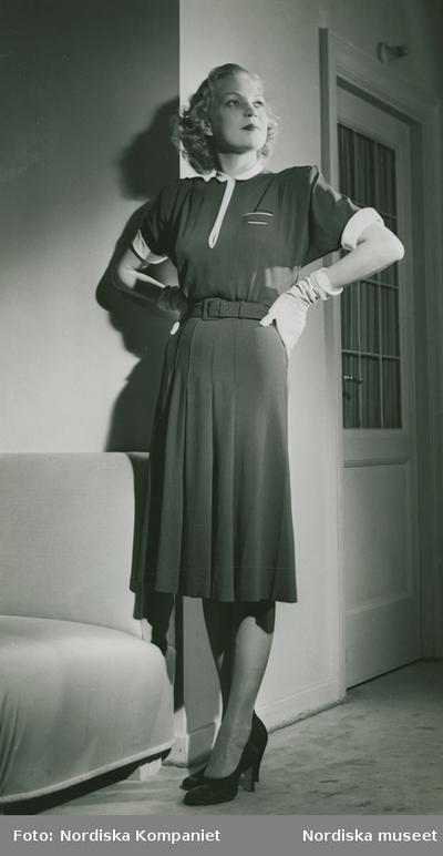 Modell i kortärmad klänning med skärp, handskar och pumps, framför en dörr och soffa.