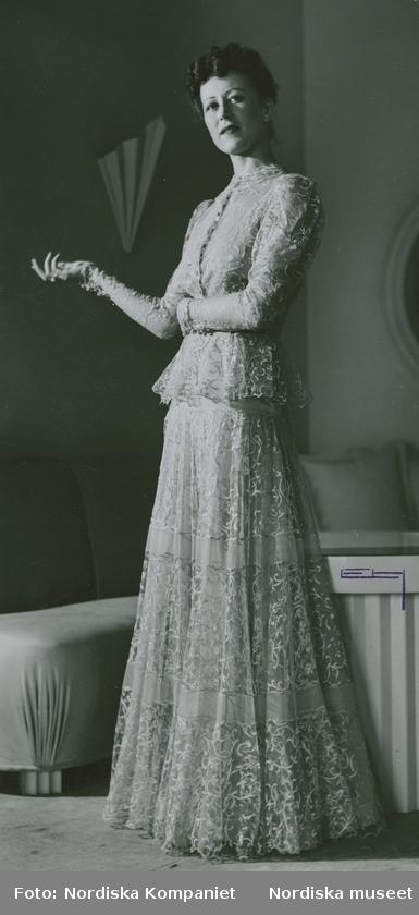 Modell i aftonklänning i mönstrat tyll, soffa i bakgrunden.