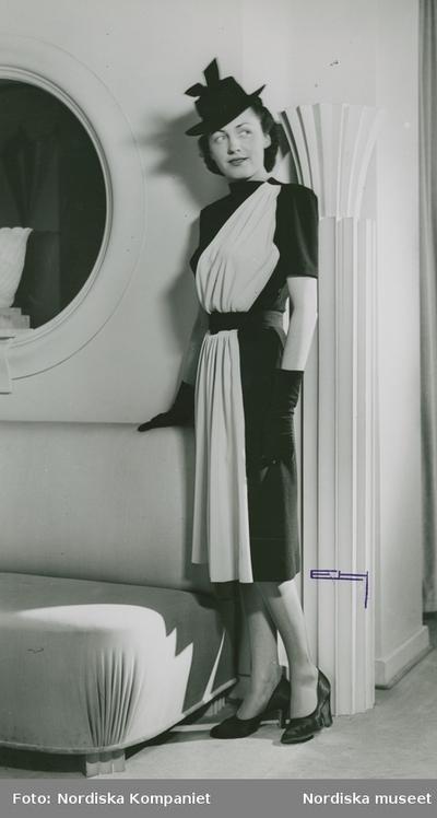 Modell i tvåfärgad klänning med skärp och draperade detaljer, handskar, hatt med ripsband och pumps. Spegel och soffa i bakgrunden.