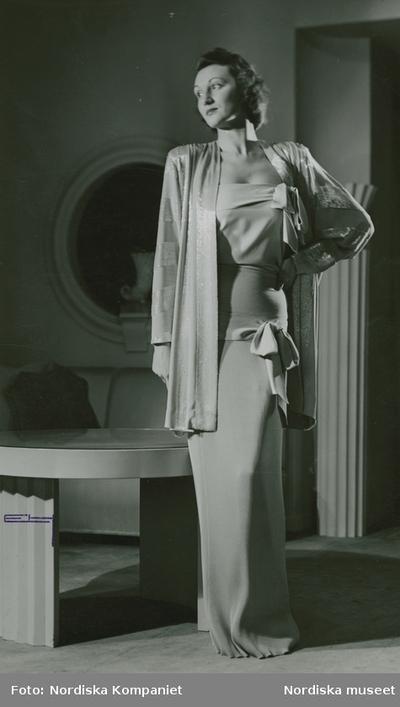 Modell i hellång klänning, dekorerad med rosetter och jacka med skimrande ränder. Bord och spegel i bakgrunden.