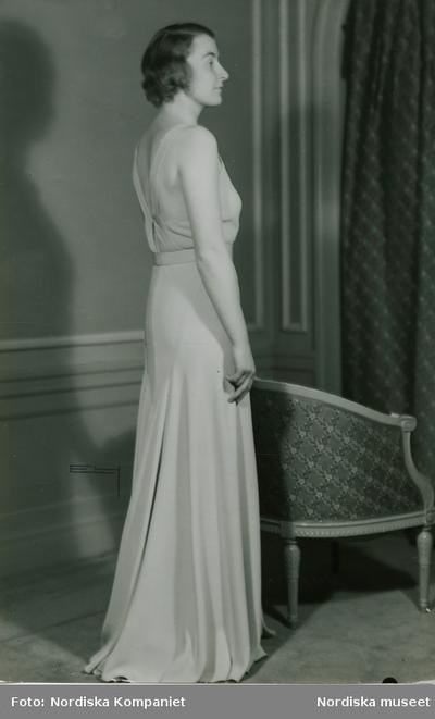 Fru B. Mixén i aftonklänning, vid en fåtölj.