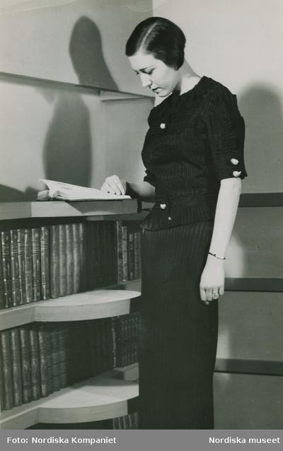 Modell i mörk kjol och mörk överdel med vita knappar, står vid en bokhylla och läser en bok.