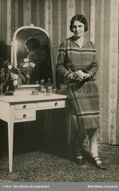 Modell i rutig dräkt demonstrerar skönhetsprodukter från Elisabeth Arden vid ett sminkbord.