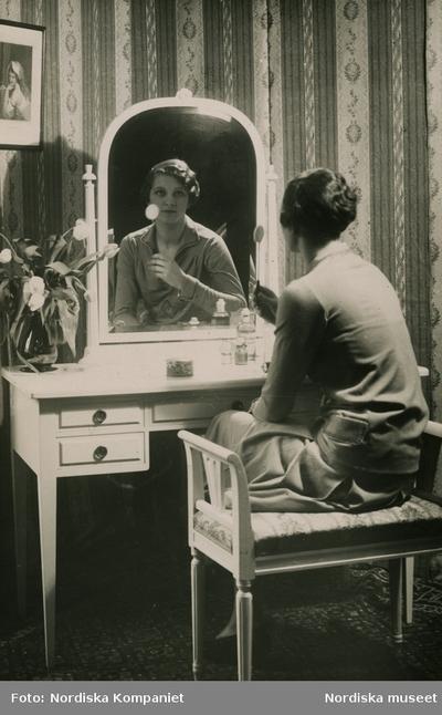 Modell demonstrerar produkter från Elisabeth Arden vid ett sminkbord.