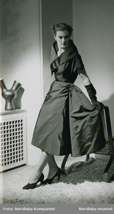 Modell i klänning med utställd kjol och hög krage, pärlhalsband, aftonhandskar och pumps, lutar sig mot en fåtölj.