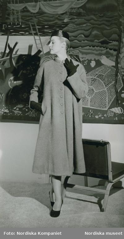 Modell i kappa, hatt, handskar och pumps. Textilkonstverk och fåtölj i bakgrunden.