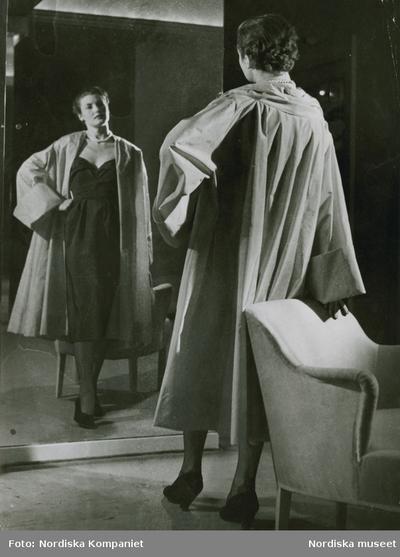 Modell i mörk klänning och karamell-skär aftonkappa i faille, speglar sig framför en fåtölj. Från Edward Molyneux för Idun.