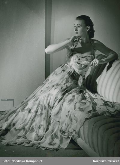 Modell i mönstrad aftonklänning i en soffa.