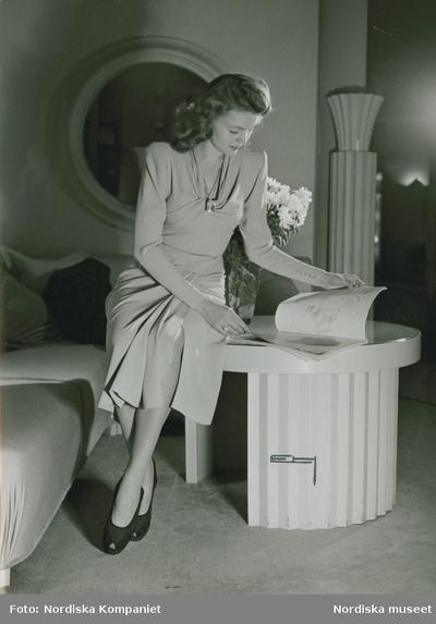Modell i klänning med draperade detaljer, halsband och ringar och skor med öppen tå, sitter på ett bord och bläddrar i en bok.
