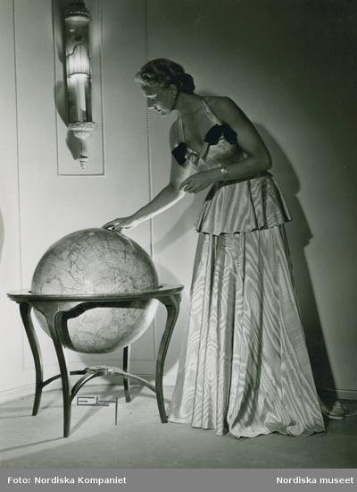 Modell i aftonklänning med volang och rosetter, tittar på en jordglob.
