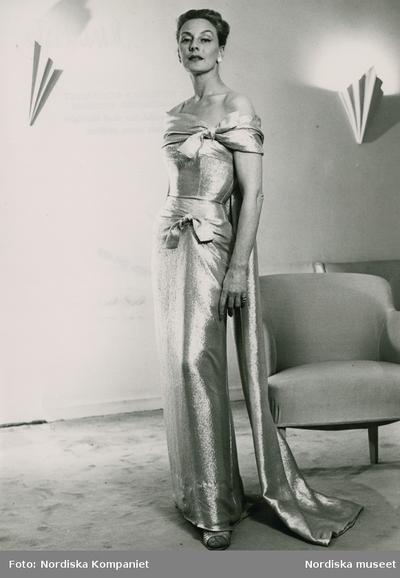 Modell i aftonklänning med rosetter, vid en fåtölj.