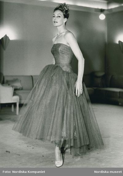 Modell i aftonklänning i tyll, fascinator och högklackade skor. Från Nordiska Kompaniet efter Lanvin. Soffor i bakgrunden.