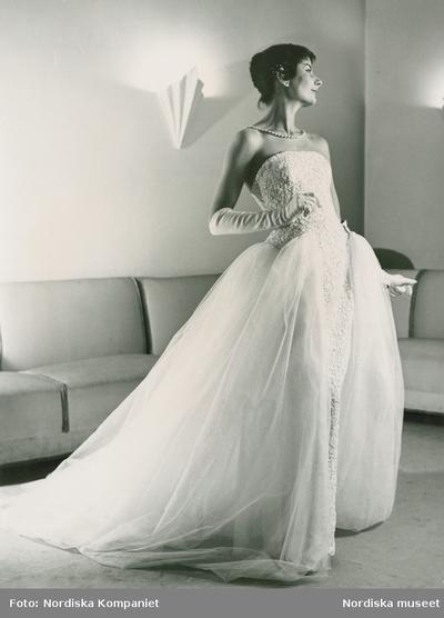 Modell i balklänning med släp, aftonhandskar och pärlhalsband. Från Nordiska Kompaniet, modell efter Jacques Heim. Soffa i bakgrunden.