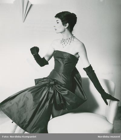 Modell i aftonklänning, operahandskar och halsband sitter på en fåtölj. Nordiska Kompaniet, modell efter Givenchy.