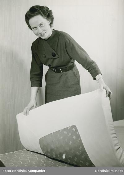 Modell i klänning med knappar och skärp lyfter på en madrass.