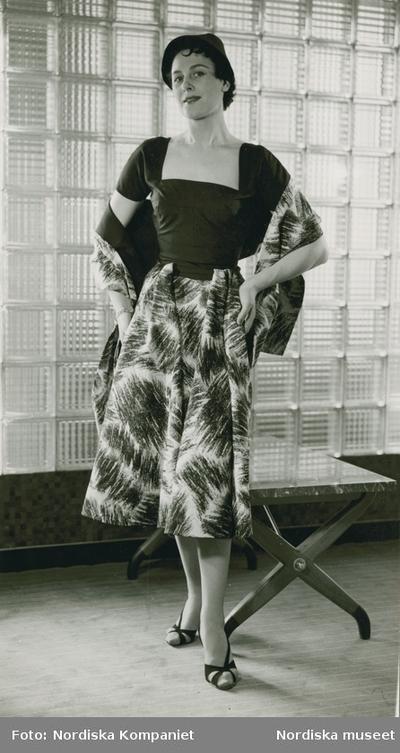 Modell i mörk överdel och mönstrad kjol och sjal i samma mönster, framför betongglas, vid ett bord. Modellbutiken.