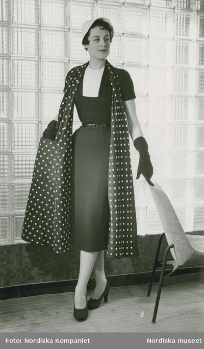 Modell i klänning, prickig sjal, hatt, handskar och pumps, framför betongglas, vid en fåtölj. Modellbutiken.