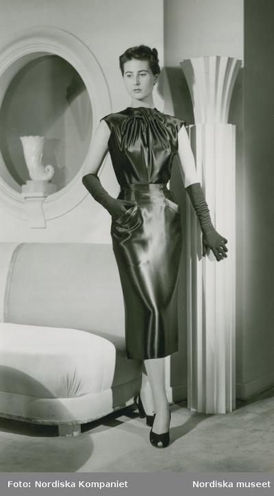 Modell i klänning, aftonhandskar och högklackade skor, vid soffa och spegel. Original från Balmain.