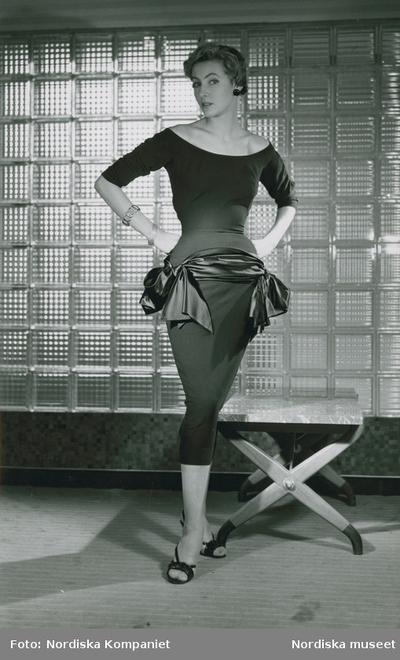 Modell i klänning med sidenband, armband, örhänge och högklackade skor, vid en pall framför betongglas.