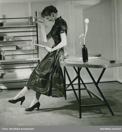 Modell i mönstrad klänning, örhänge, armband och pumps, läser i en bok, lutad mot ett bord.