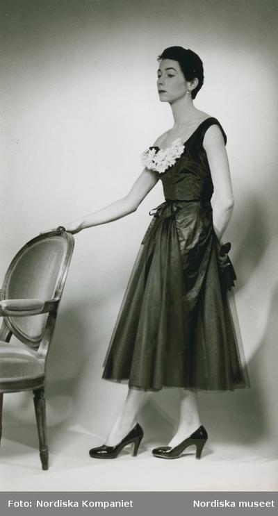 Modell i klänning med blomstergarnityr och pumps vid en stol.